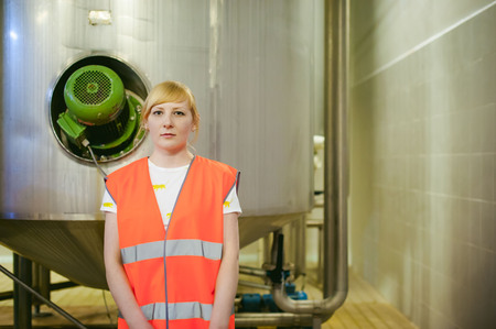 Female worker on beer factory. portrait woman in robe, standing on background line Food production, Inspection management control Equipment for production and bottling finish product end-user buyer