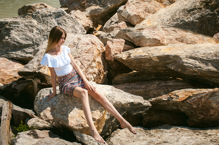 Portrait of slender young woman on stones near the sea. Beautiful girl is resting on coast, enjoying outdoor recreation. Graceful long thin tender arms and legs