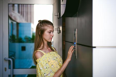 Photo pour woman dials an apartment code on an electronic doorphone panel - image libre de droit