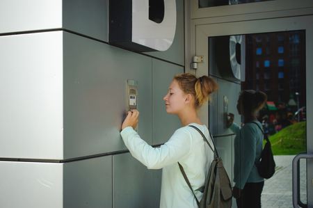 Photo pour young blond teenager schoolgirl dials the code for a call over the intercom - image libre de droit