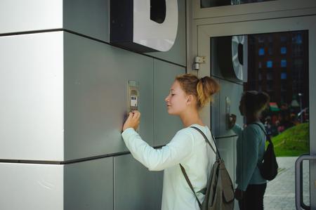 Foto für young blond teenager schoolgirl dials the code for a call over the intercom - Lizenzfreies Bild