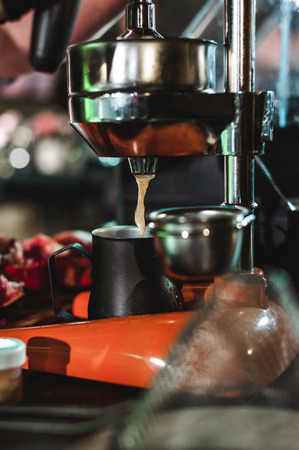 man's hand squeezes juice from citrus on a professional mechanical juicer. championship among coffee houses, members of teams show barista's skill, prepare drinks, teamwork.