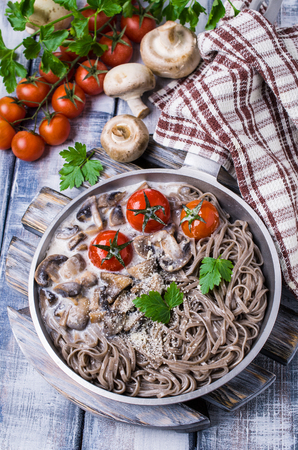 Dark pasta with vegetables in white sauce on wooden background. Selective focus.
