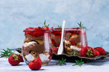 Cold dessert with strawberry jelly, yogurt and cookies in glass. Selective focus.