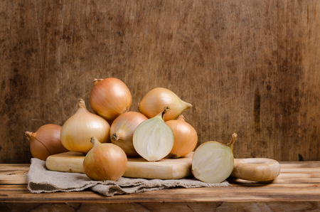 Foto de Large raw organic onions on wooden background. Selective focus. - Imagen libre de derechos