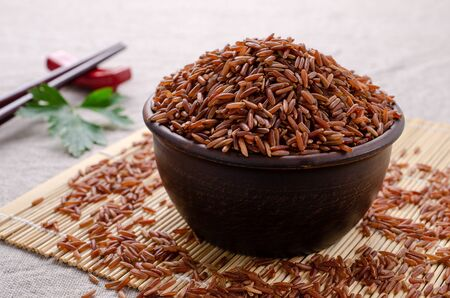 Foto de Red unpolished rice in ceramic bowl on textile background. Selective focus. - Imagen libre de derechos
