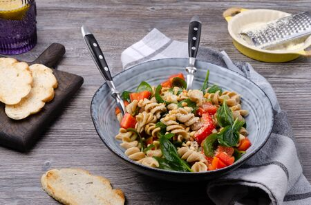 Foto für Brown pasta with vegetables, nuts and cheese in a dish on a wooden background. Selective focus. - Lizenzfreies Bild