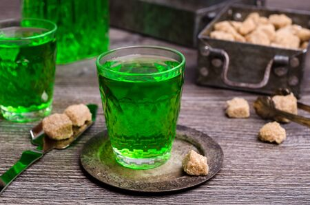 Photo pour Green liquid in a glass with sugar cubes on a dark wooden background. Selective focus. - image libre de droit