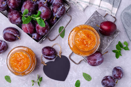 Photo for Yellow plum jam in a glass jar on a gray stone background with fresh fruit. Selective focus. - Royalty Free Image