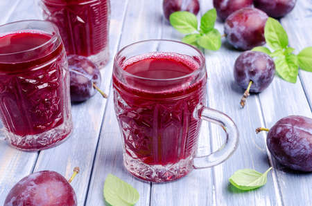 Photo pour Red plum juice in glass on a blue wooden background with fresh fruit. Selective focus. - image libre de droit