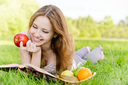 Charming girl with apples lies on green grass and reads book.