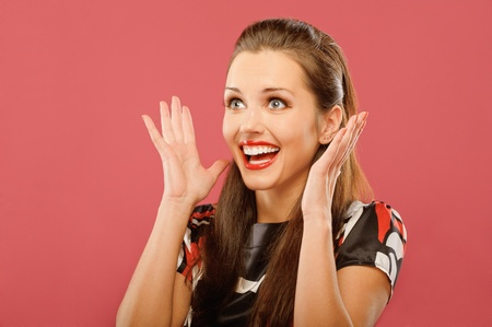 Young beautiful woman delightfully plants hands and is surprised, on red background.