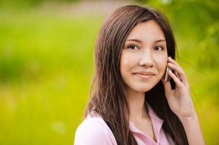 Portrait of young beautiful woman talking on telephone at summer green park.