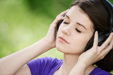 Close-up portrait of young pensive woman listening to music at summer green park.