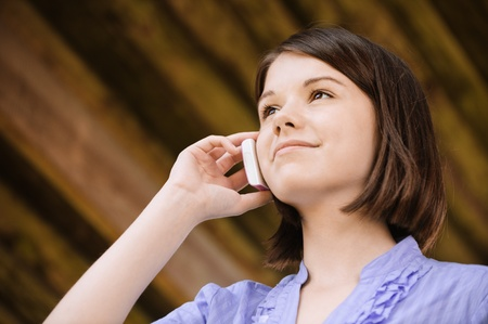 Portrait of young beautiful smiling woman talking on telephone.