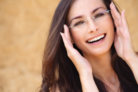 Close-up portrait of young beautiful brunette woman wearing glasses against beige background.