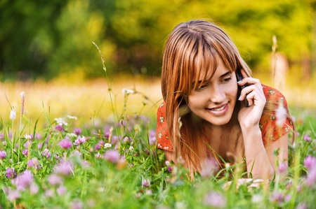 Portrait of young beautiful woman lying on grass and speaking on telephone at summer green park.