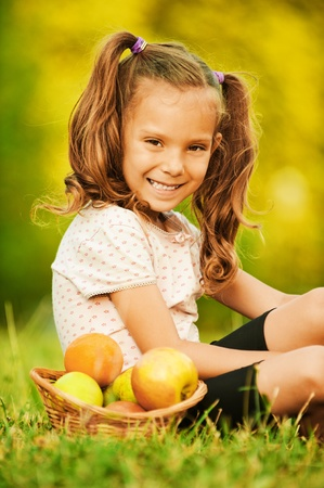 Portrait of pretty little girl wearing white t-shirt and black shorts, sitting near basket full of fruits on grass at summer green park.