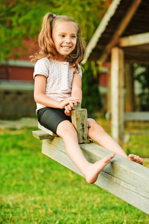 Portrait of little smiling girl wearing white t-shirt and shorts having fun on seesaw at summer green park.