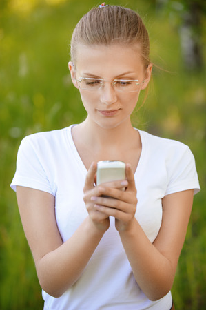 Portrait of young beautiful fair-haired woman wearing white dress looking at telephone at summer green park.