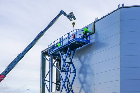 Photo for sandwich panels wall mounting using crane and scissor lift - Royalty Free Image