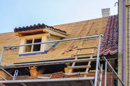 Photo pour repair of the roof structures of a beautiful historic wooden house and replacement of clay tiles - image libre de droit