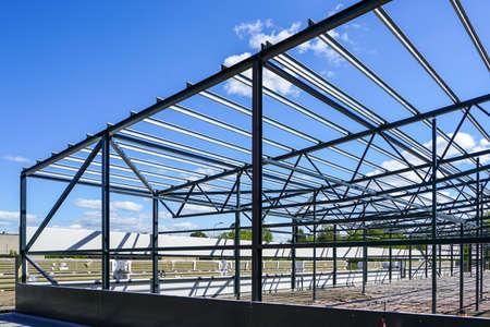 Foto de construction of a new modern industrial building, metal truss frame on a background of blue sky - Imagen libre de derechos