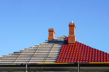 Photo pour replacement of the roofing of a residential house on a background of blue sky, half changed, half not yet - image libre de droit