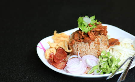 Fried rice Shrimp paste with pork and fried egg in plate on black table. Thai food (Kao Cluk Ka Pi).