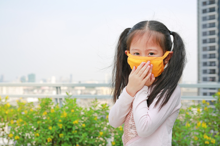 little child girl wearing a protection mask against PM 2.5 air pollution in Bangkok city. Thailand.