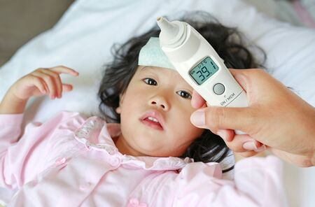 Closeup mother hand takes temperature for her daughter with high pressure of ear thermometer on bed at home.
