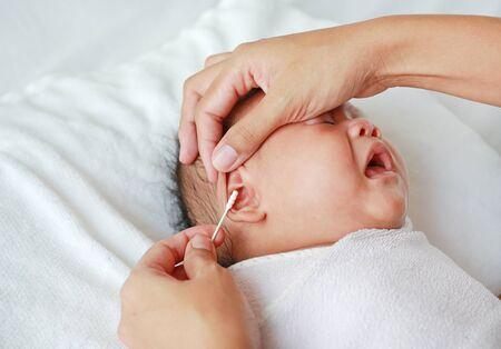Photo pour Close-up mother use cotton bud to clean baby ear. - image libre de droit