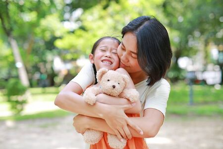 Photo pour Portrait of happy Asian mother cuddle daughter and hugging teddy bear doll in the garden. Mom and child girl with love and relationship concept. - image libre de droit