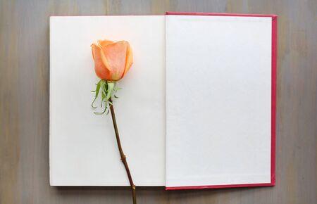 Foto de Rose flower on open book against wood background. - Imagen libre de derechos