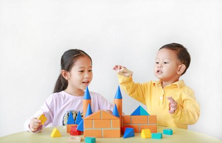 Photo pour Asian little child girl and baby boy playing a colorful wood block toy on table over white background. Sister and her brother playing together. - image libre de droit