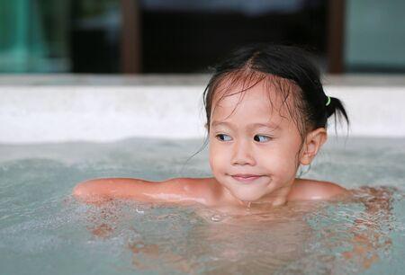 Photo pour Adorable little child girl lying in the hot tub. - image libre de droit