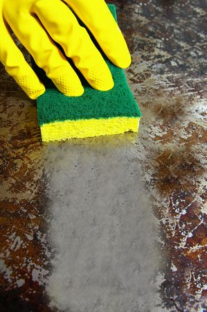 sponge wiping a dirty metal surface clean