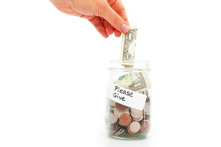 hand putting a dollar into a donation jar