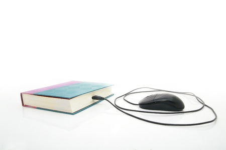 PC mouse plugged into a book, on white