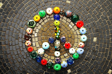 colorful glass beads peace sign on mosaic tiles