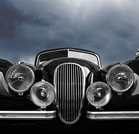 Vintage car front view with dark clouds