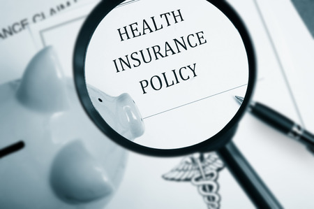 Magnifying glass over health insurance policy and piggy bank