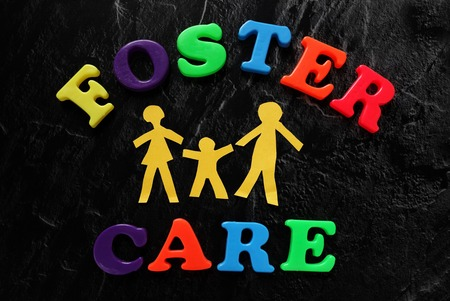 Paper cutout family with Foster Care letters