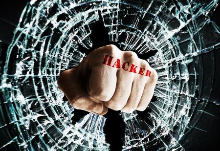 Photo pour Fist with Hacker text punching thru a glass window  -- cyber crime concept - image libre de droit