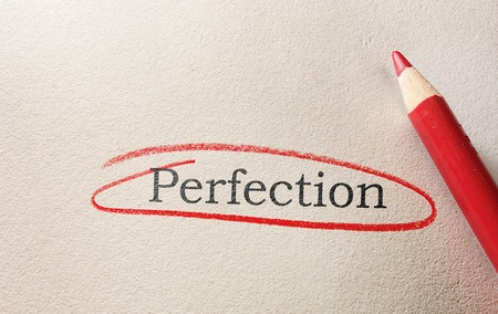 Perfection text circled in red pencil, on textured paper