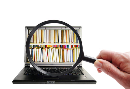 Hand with magnifying glass looking at laptop with books