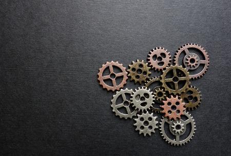 Assorted metal gears on blank dark background