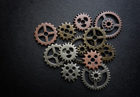 Small metal gears arranged on black background