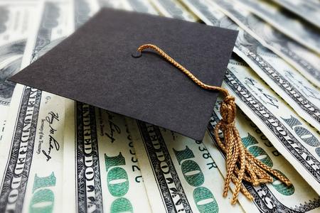 Foto de Mini graduation mortar board cap on money -- education cost or scholarship concept - Imagen libre de derechos