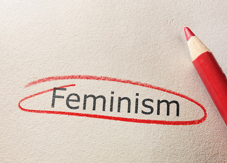 Feminism text circled in red pencil on textured paper